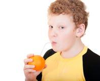 Pojke som dricker orange fruktsaft Arkivfoto