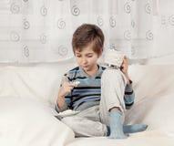 Pojke som dricker te och äter kex Arkivfoton