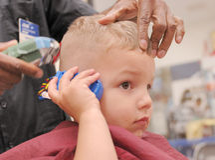 pojke som får frisyrlitet barn Arkivfoto