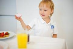 Pojke som förbereder frukosten i vitt kök Royaltyfri Fotografi