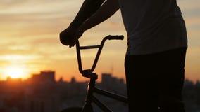 Pojke som förbereder sig för ritten med hans bmx som ser solnedgång stock video