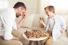 Pojke som firar framgång i schacklek med fadern nära förbi Arkivfoto