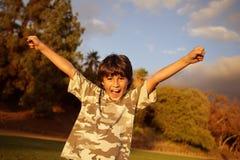 Pojke som firar på solnedgången Royaltyfria Bilder