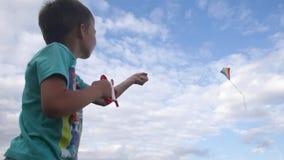 Pojke som flyger en drake i himmel arkivfilmer