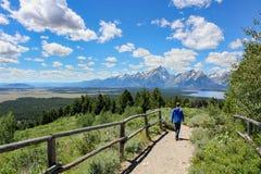 Pojke som fotvandrar med sjö- och bergsikt fotografering för bildbyråer