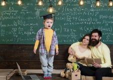 Pojke som framlägger hans kunskap till mamman och farsan Det smarta barnet i doktorand- lock gillar att utföra Föräldrar som lyss Arkivfoton