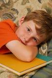 pojke som gör den sömniga läxan Arkivbild