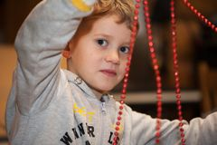 Pojke som gör julgarnering av röda pärlor royaltyfria bilder