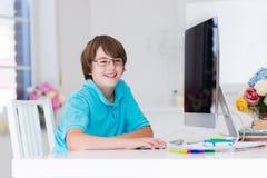 Pojke som gör läxa med den moderna datoren Fotografering för Bildbyråer