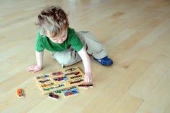 pojke som gör pusselbarn Arkivbild