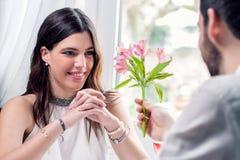 Pojke som ger blomman till flickan i restaurang royaltyfria bilder