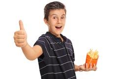 Pojke som ger upp en tumme och rymmer en påse av småfiskar Royaltyfria Foton