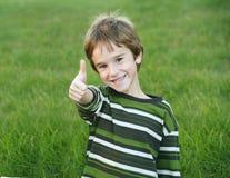 pojke som ger upp tum Arkivfoton