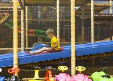 Pojke som glider på lekplats Arkivbild