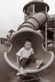 Pojke som glider på lekplats Arkivfoton