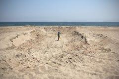 Pojke som gräver en enorm gropleksakskyffel royaltyfri foto