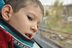 Pojke som håller ögonen på staden till och med fönstret Arkivbild