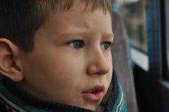 Pojke som håller ögonen på staden till och med fönstret Fotografering för Bildbyråer