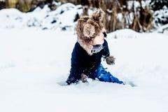 Pojke som har gyckel i snön Arkivfoto