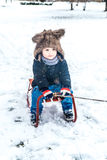 Pojke som har gyckel i snön Royaltyfri Foto