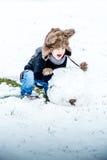 Pojke som har gyckel i snön Arkivbild