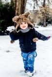 Pojke som har gyckel i snön Arkivbilder