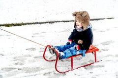 Pojke som har gyckel i snön Arkivfoton