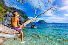Pojke som har gyckel på den tropiska stranden Arkivbilder