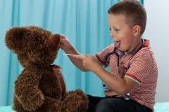 Pojke som har gyckel på pediatricians kontor Arkivfoton