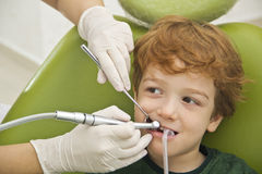 Pojke som har hans tänder att undersökas av tandläkaren Arkivfoto