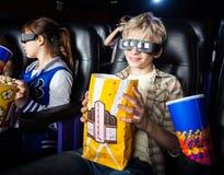 Pojke som har mellanmål, medan hålla ögonen på filmen 3D med Royaltyfri Fotografi