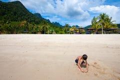 Pojke som har rolig det fria som spelar i sanden vid stranden i den tropiska ön Royaltyfria Foton