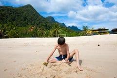 Pojke som har rolig det fria som spelar i sanden vid stranden i den tropiska ön Royaltyfria Bilder