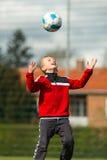 Pojke som heading till hans fotbollboll Royaltyfria Bilder
