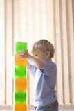 Pojke som hemma bygger färgrika tegelstenar Royaltyfri Foto