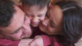 Pojke som hemma kysser och omfamnar föräldrar lager videofilmer