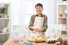 Pojke som hemma lagar mat och att göra deg, bullar och kakor royaltyfri fotografi