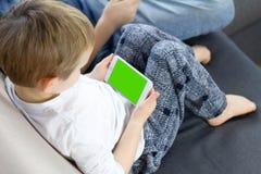 Pojke som hemma sitter och använder den mobila smarta telefonen med den gröna skärmen Stäng sig upp av tummen som bläddrar upp ti royaltyfria bilder