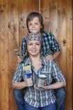 Pojke som hjälper hans moder som målar hjälpmedelskjulet Royaltyfri Foto