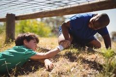 Pojke som hjälper hans vän under hinderkurs royaltyfri bild