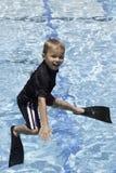 Pojke som hoppar av av dykningbräde med flipper Royaltyfri Fotografi