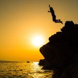 Pojke som hoppar till havet Kontur som skjutas mot solnedgånghimlen Arkivbild