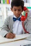 Pojke som imiterar som affärsmanhandstil på boken, medan genom att använda landlinen Arkivfoto