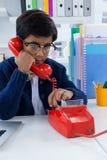 Pojke som imiterar som affärsmannen som använder landlinjen telefon Arkivfoton