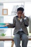 Pojke som imiterar som affärsmannen som gör en gest, medan tala på smartphonen Royaltyfria Bilder