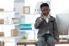 Pojke som imiterar som affärsmannen som talar på den smarta telefonen Arkivfoton