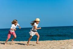 Pojke som jagar flickvännen på stranden. Arkivbild