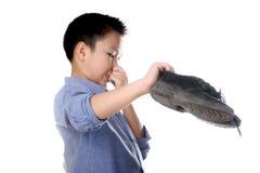 Pojke som känner sig olycklig med den vita sockan för dålig lukt arkivfoto