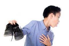 Pojke som känner sig olycklig med den vita sockan för dålig lukt royaltyfri bild