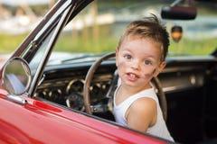 Pojke som kör med hans bil Arkivbild